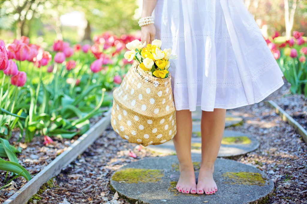 A woman in a white dress stands barefoot on a garden path. She is visible from the waste down only and holds a colorful basket of flowers in her right hand.