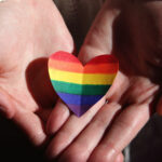 Caucasian hands holding a heart that has been colored with a rainbow.