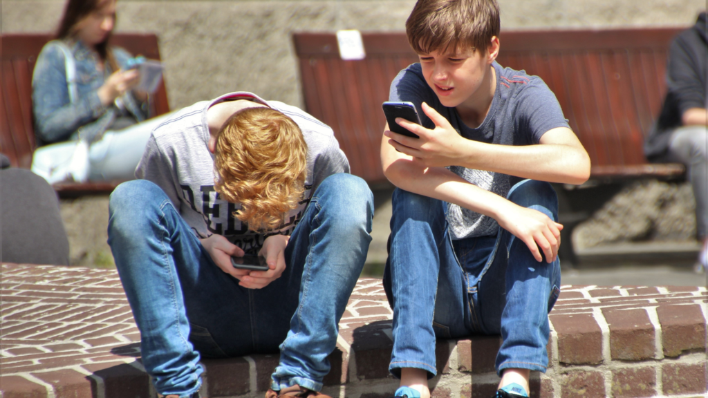 Two teen boys sit on a curb in an outdoor location. They are both looking at cell phones.